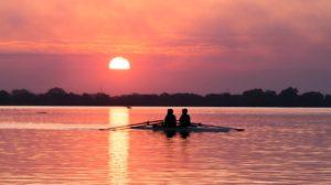 Amigos viendo una puesta de sol en un lago.