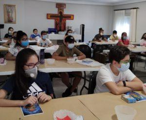 Hay varios niños en la aula parroquial haciendo manualidades.