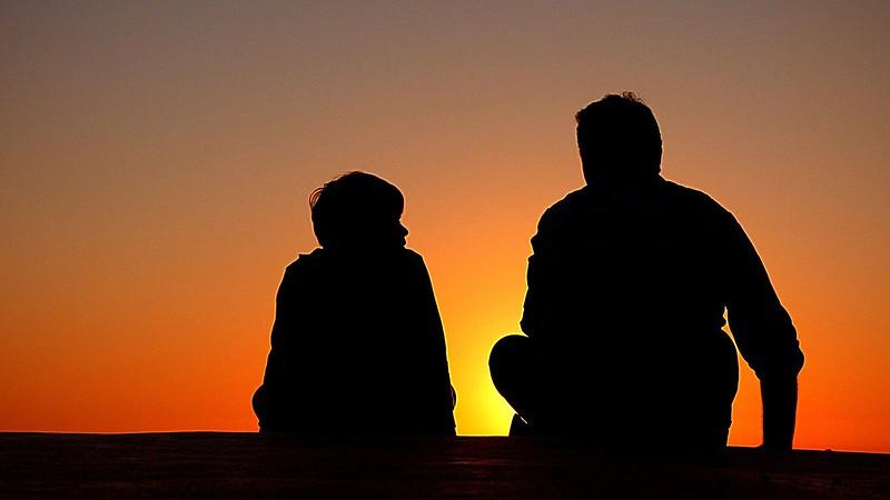 Dos personas en una puesta de sol hablando.